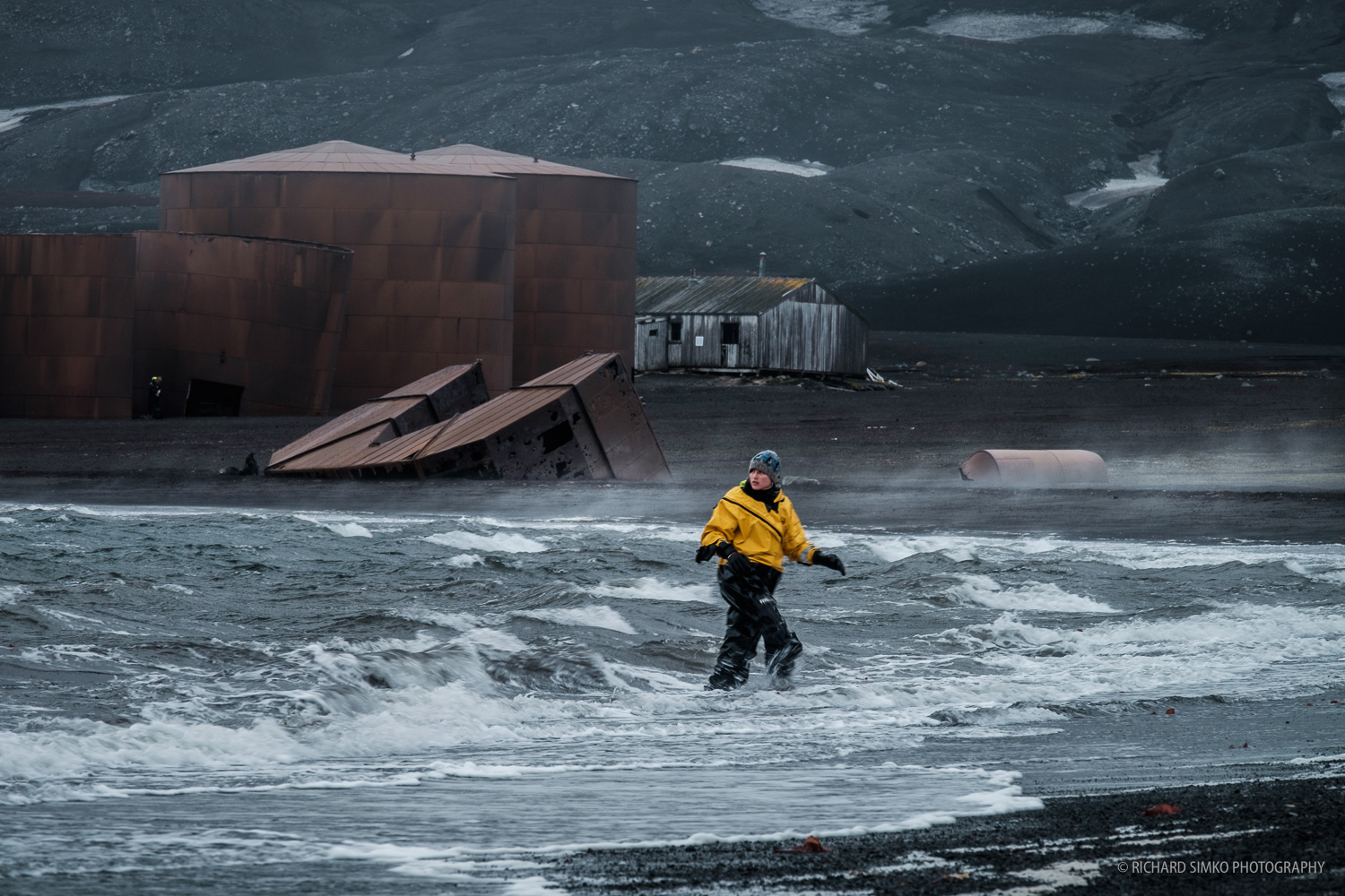 Belen in her wet suit sees of a zodiac while trying to keep ballance in rather rough swell in Whalers Bay at Deception Island