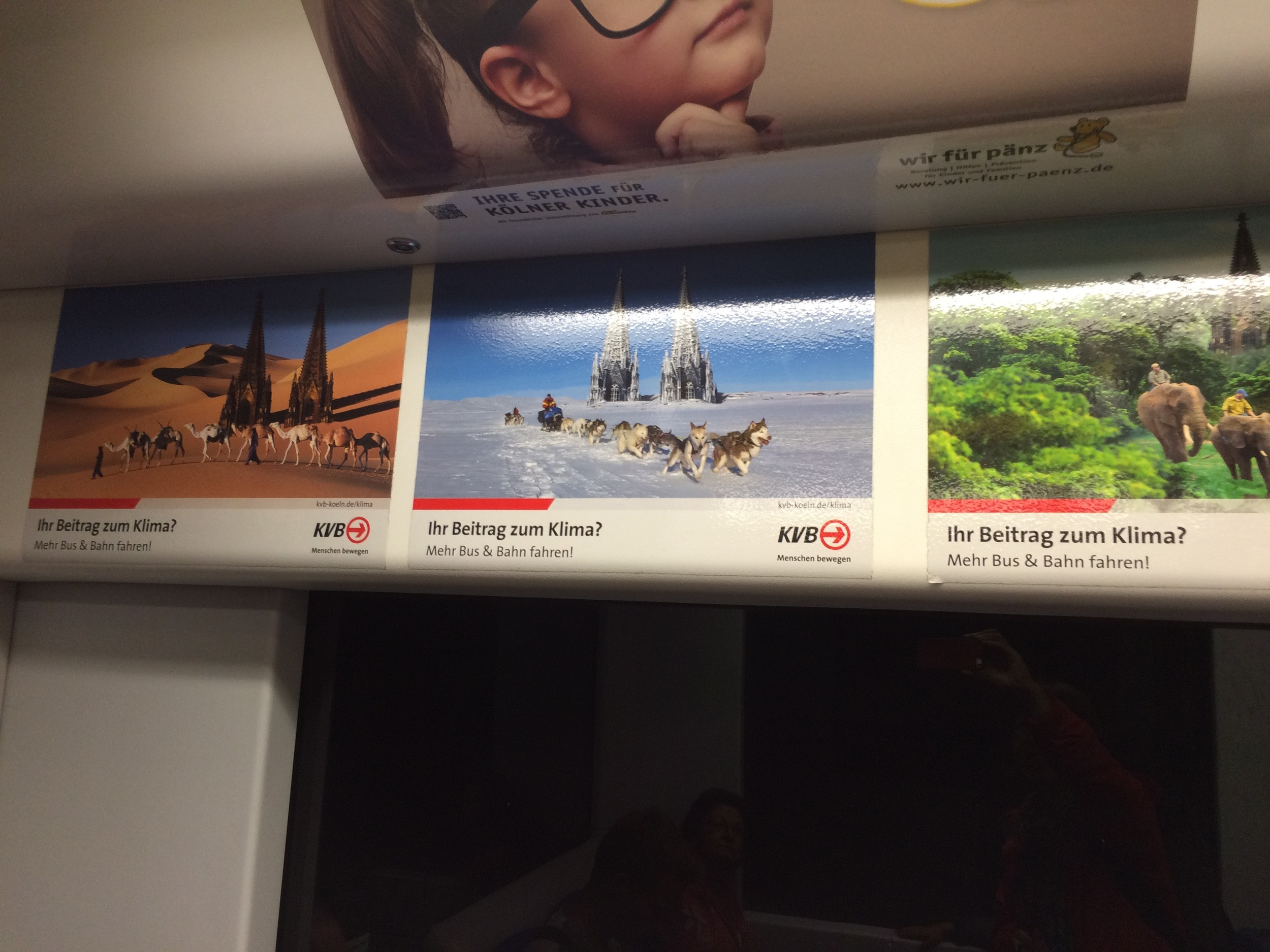 """Signs in the Cologne metro, showing the Cologne """"Dom"""" cathedral overwhelmed by climate chaos. The signs say:""""What are you doing for the climate? Riding the bus & train more!"""""""