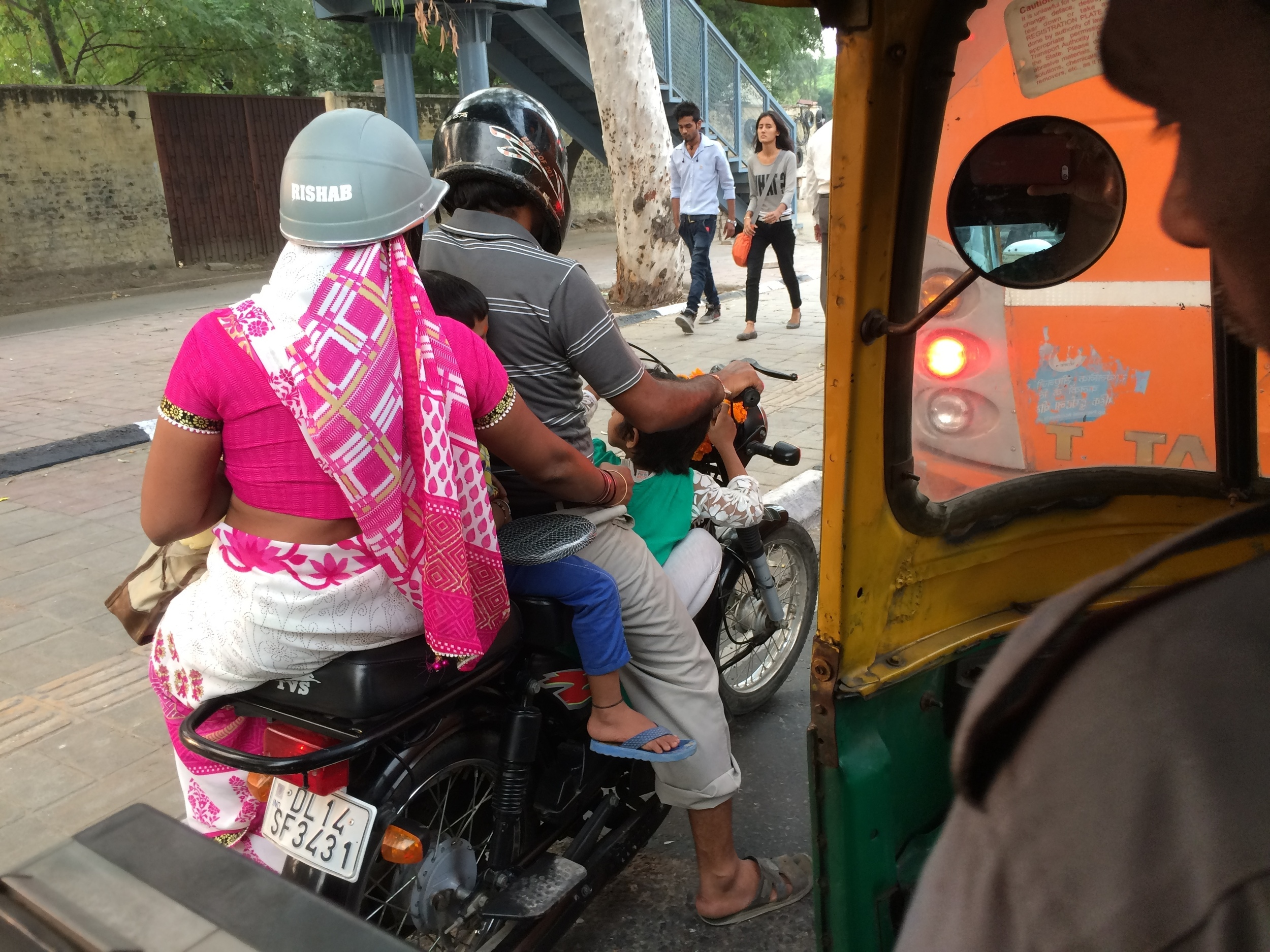 Four riders, two helmets, one motorbike - in New Delhi, India.