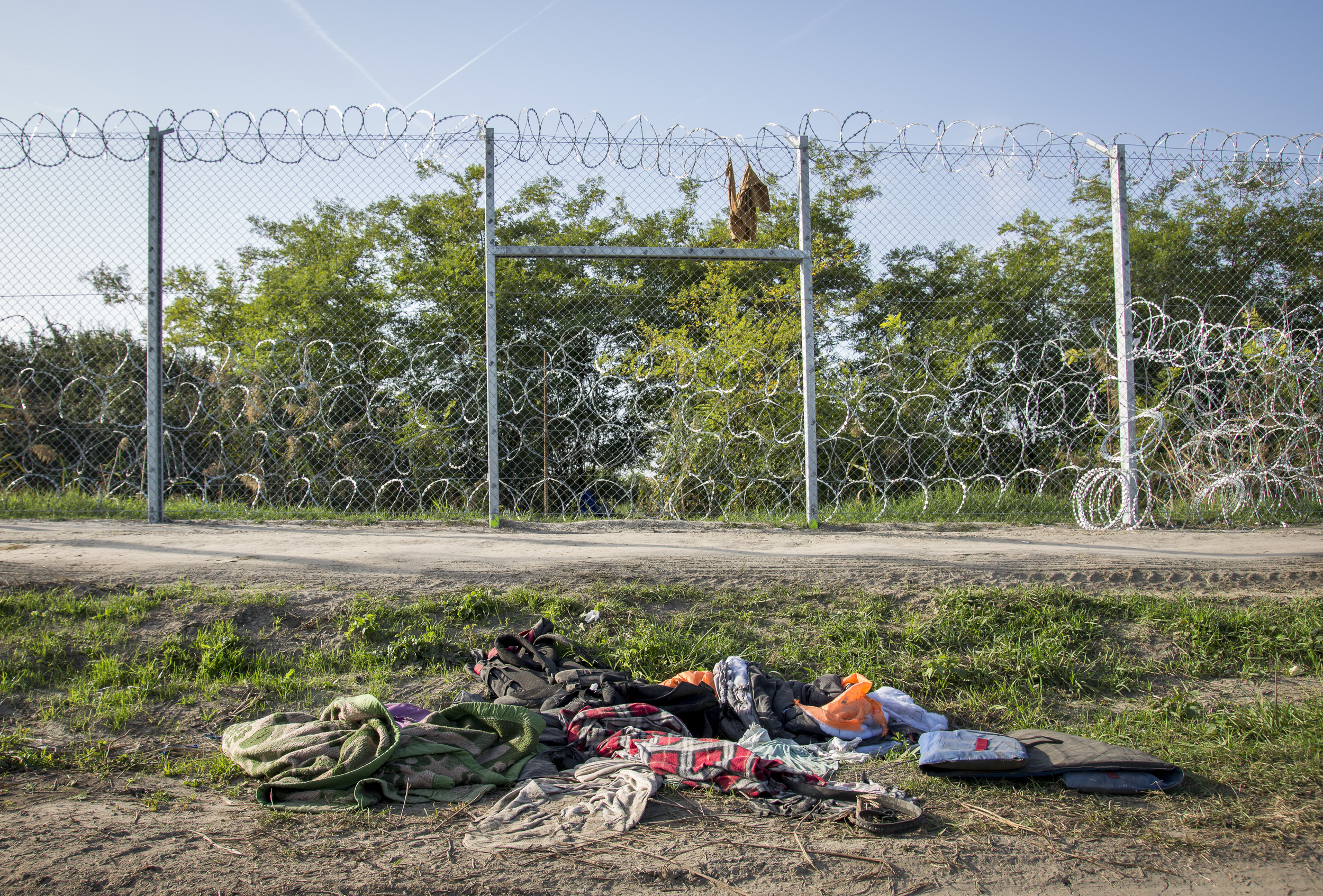 Along the fence in Roszke, Hungary,are the traces of the refugees. Someone have left the life jacket they used across the Mediterranean.