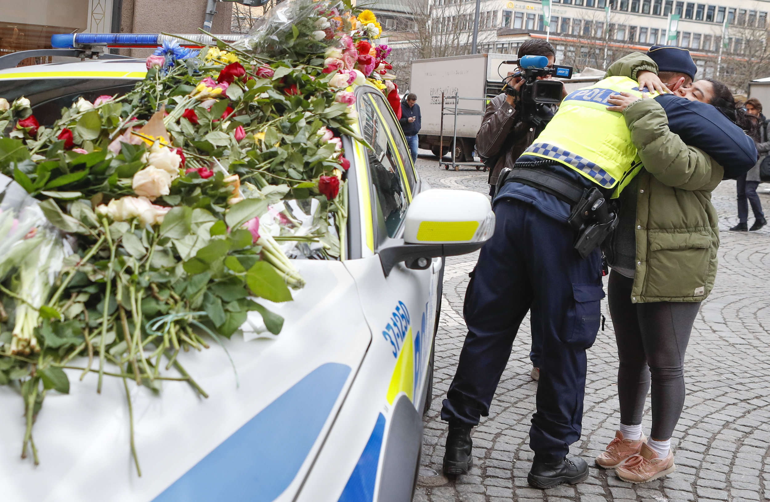 A young girl gives a cop a hug the day after the terrorist attack on Drottninggatan in Stockholm, Sweden.  Five people were killed including an eleven-year-old girl and 14 others were seriously injured.