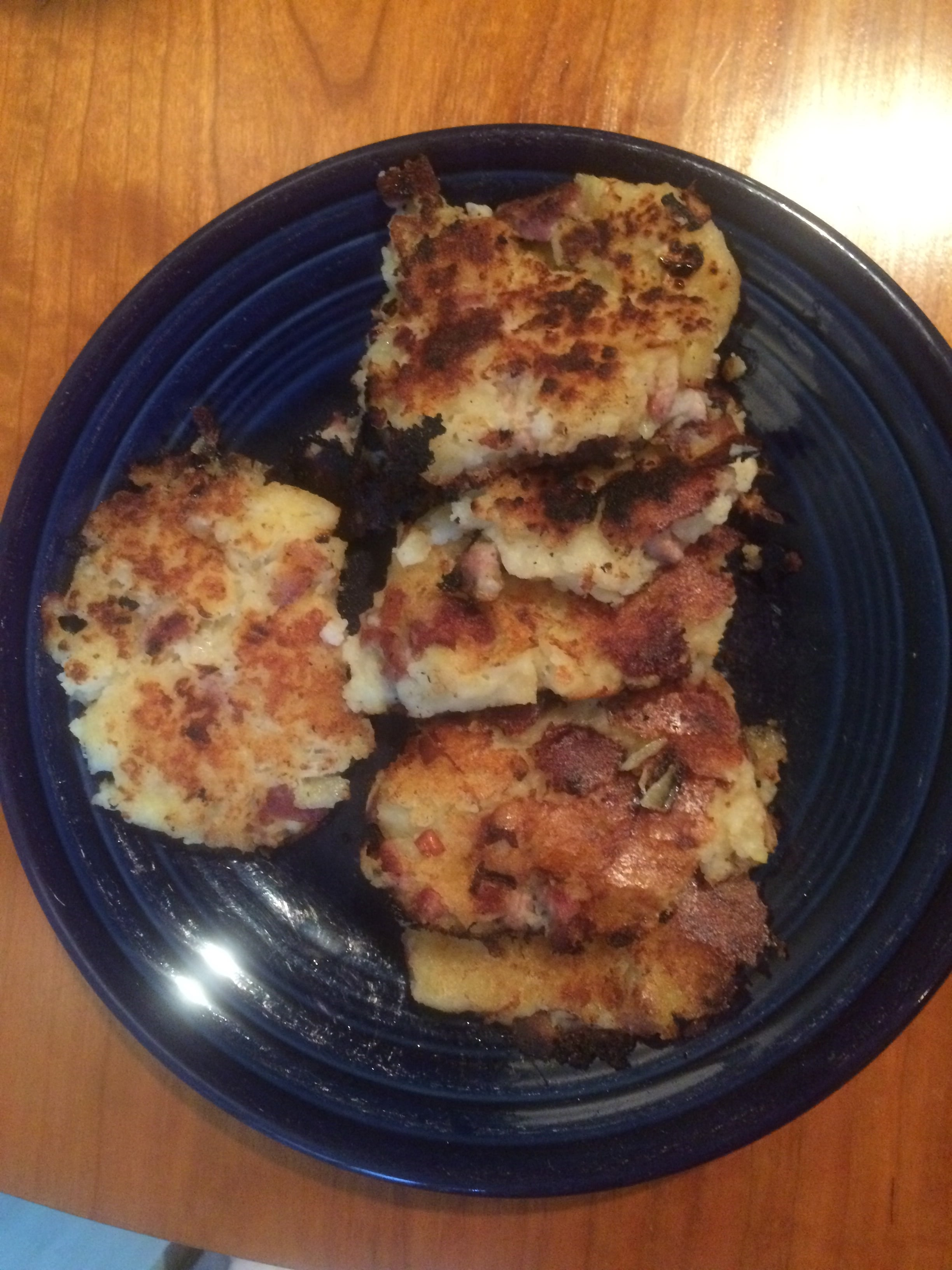 A slightly messy mashed potato cake with ham bits and chopped onion.