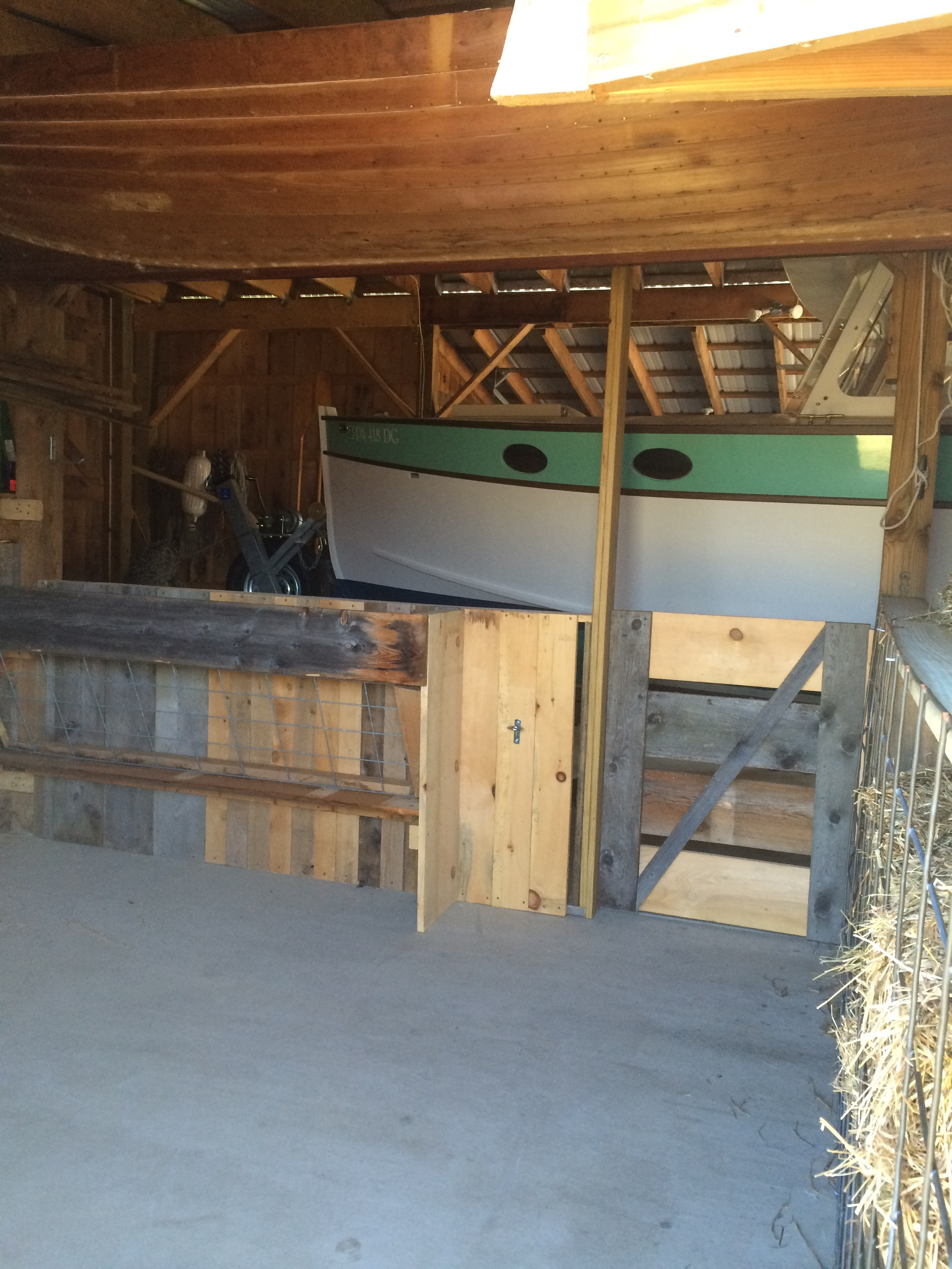 The hay feeder and water bucket are accessible from outside the pen.