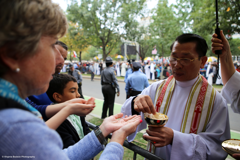 Un sacerdote distribuyendo entre la multitud hostias, o pan de comunión.