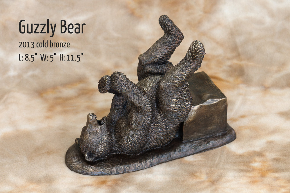 """Guzzly Bear. A happy-go-lucky bear enjoying a bottle of wine by Terrence Robertson-Fall. 2013 Cold Bronze. Dimensions are 8.5"""" x 5"""" x 11.5"""