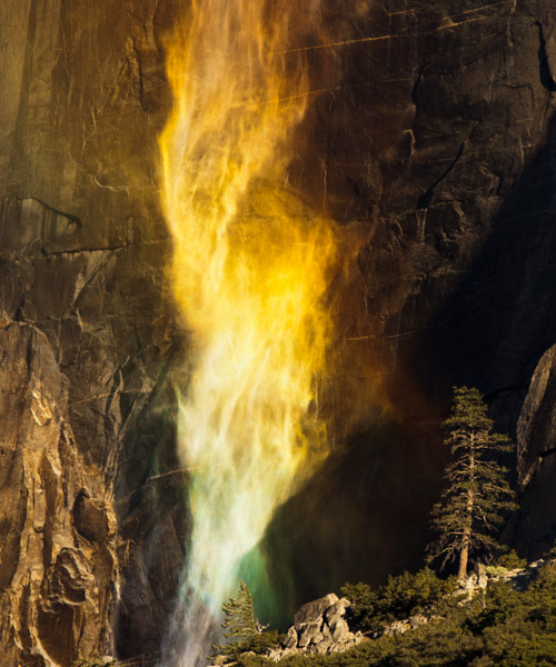 Firetwist.  Photograph by Terrence Robertson-Fall.  Blazing like a twister of fire, the whispy, late fall Yosemite Falls swims through a sunlit rainbow in Yosemite National Park.  At this time of year, the water flow is at it's lowest, and the falls aren't much more than a mist that are easily blown about by the breezes.