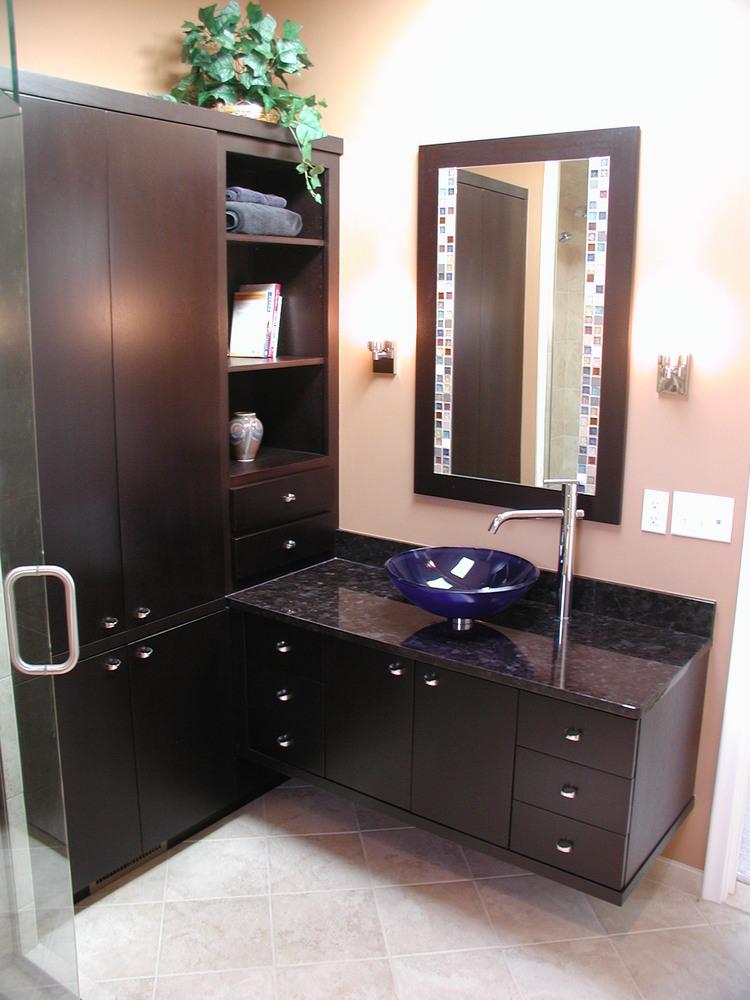 Bathroom design featuring unique blue glass vessel sink.