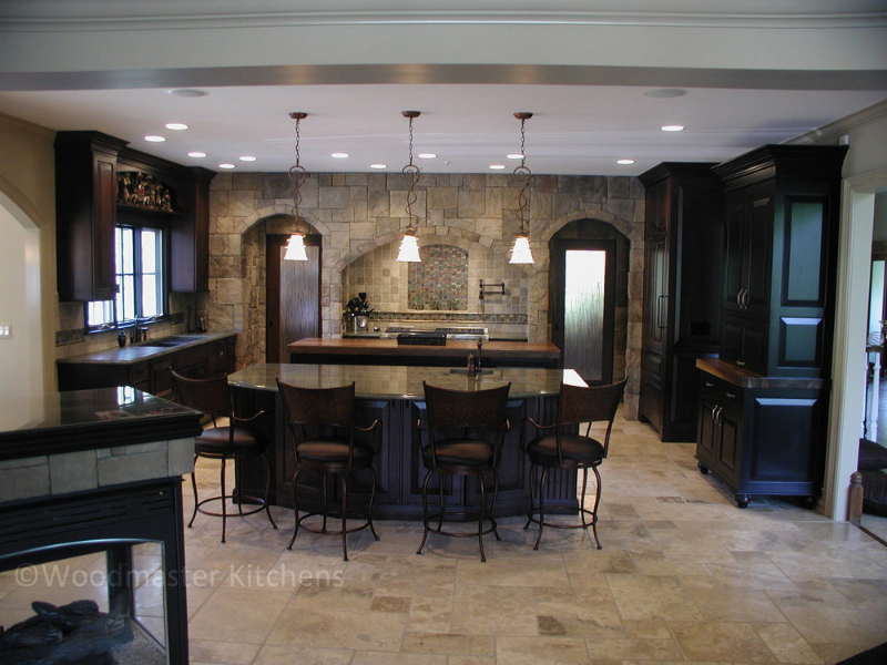 Dramatic and sophisticated kitchen design with a unique stone accent wall and niche.