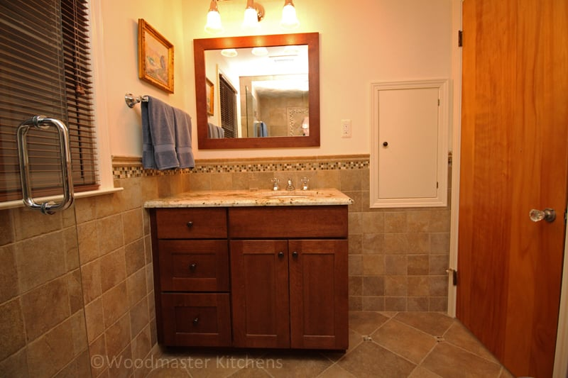 Bathroom design with a mirror framed in wood matching the vanity cabinet.
