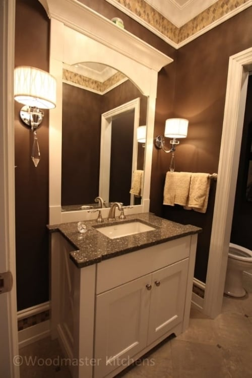 Bathroom design with a white vanity cabinet and matching framed mirror.