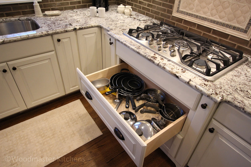 Kitchen design featuring a pull out drawer for pots and pans.