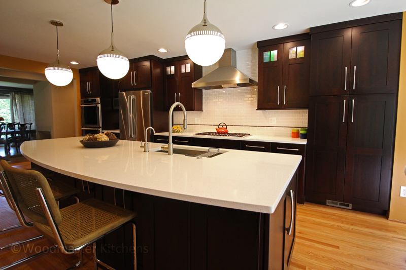 Contemporary kitchen design with dark wood kitchen cabinets and white countertop.