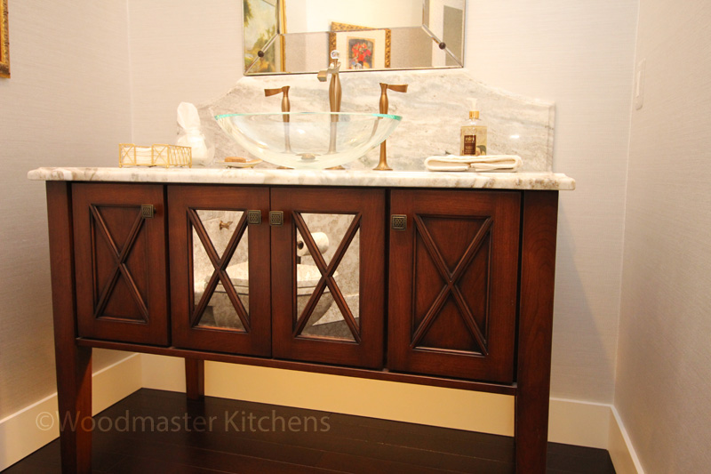 Powder room with furniture style vanity with mirrored panels.