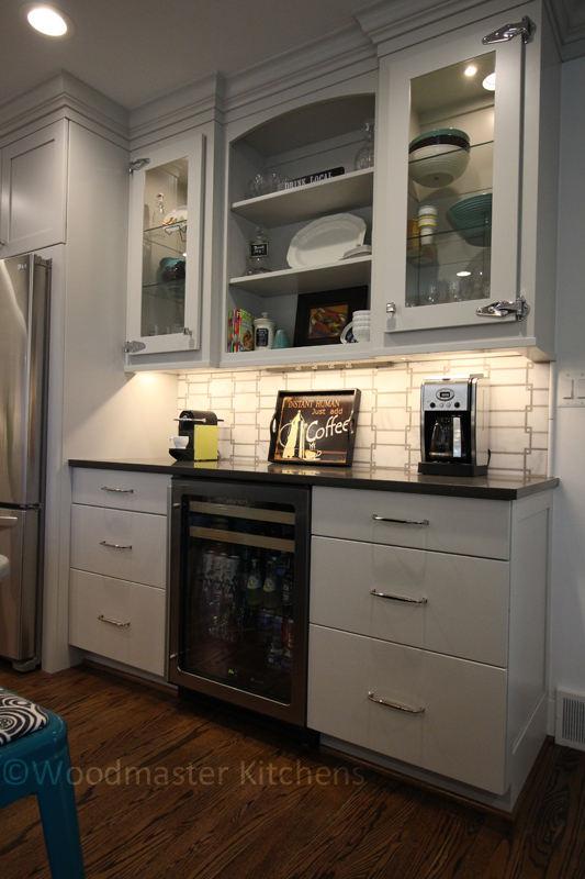 Beverage bar with undercounter refrigerator, coffee maker, and storage.