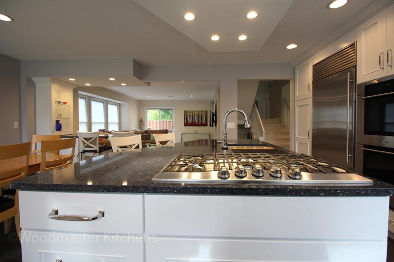 White kitchen cabinets with dark gray quartz countertopo