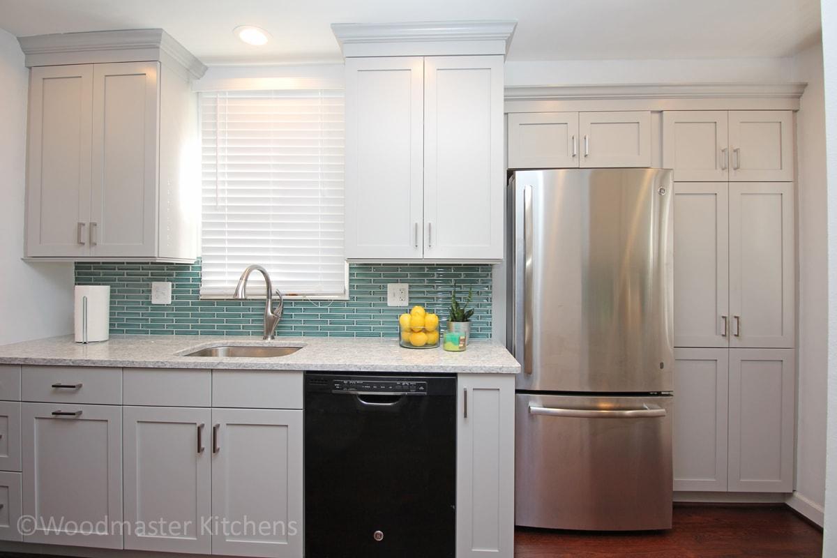 white kitchen design with stainless steel refrigerator