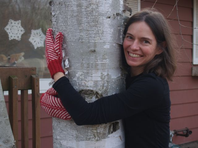 Susan hugs a tree in newly knit mittens.