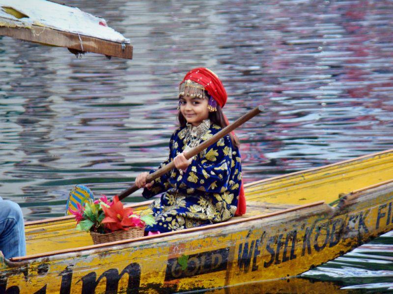 Kashmiri girl wearing a Phiran on a Shikara boat.