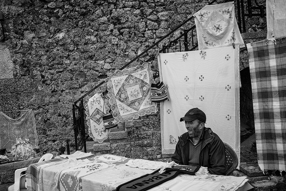 Man selling Table cloths in Kruja, Albania