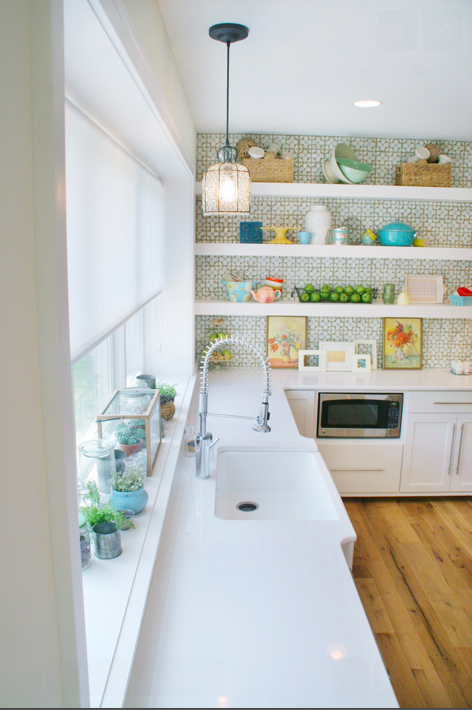 Beautiful solid white countertops in a kitchen by Green Apple Design, where the movement and interest comes from the omg-gorgeous backsplash, accessories, and graining in the floor.  Photo  courtesy  Solomon Building Group
