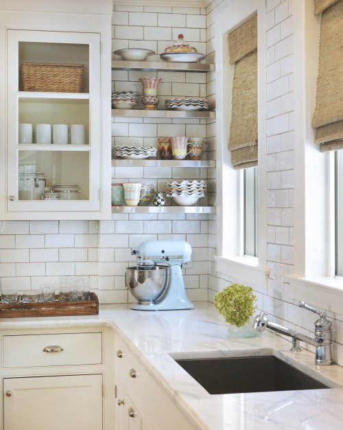 Another beautiful kitchen with white countertops, but these have a marble movement that complements the stainless shelves and all-white accessories. Photo courtesy  Taste Interior Design.