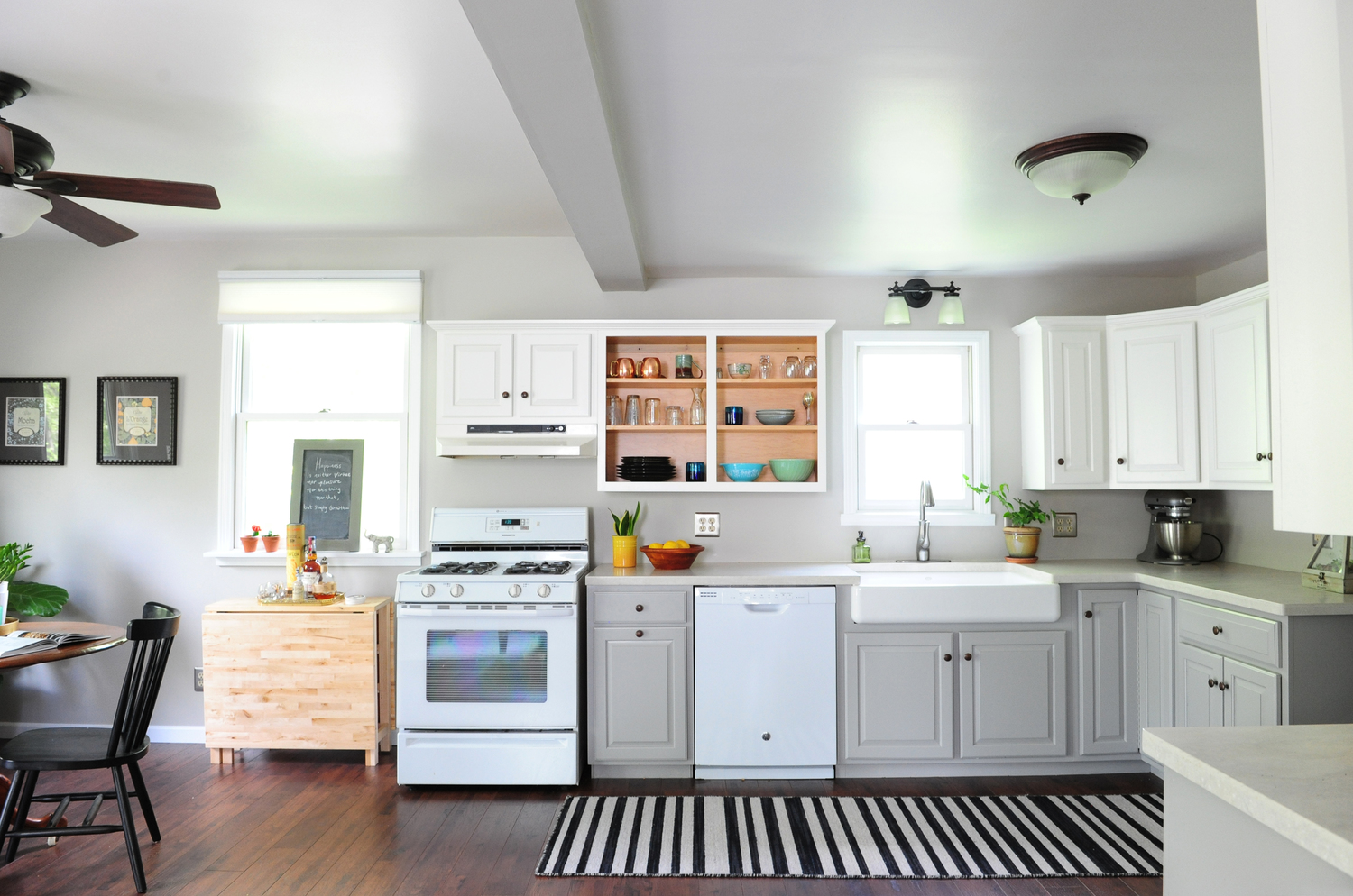Simple, affordable kitchen update. Cabinets painted; vinyl floors swapped to plank laminate; drop-in stainless steel sink replaced with an apron farmhouse sink; laminate countertops upgraded to solid surface. The before can be found  here .