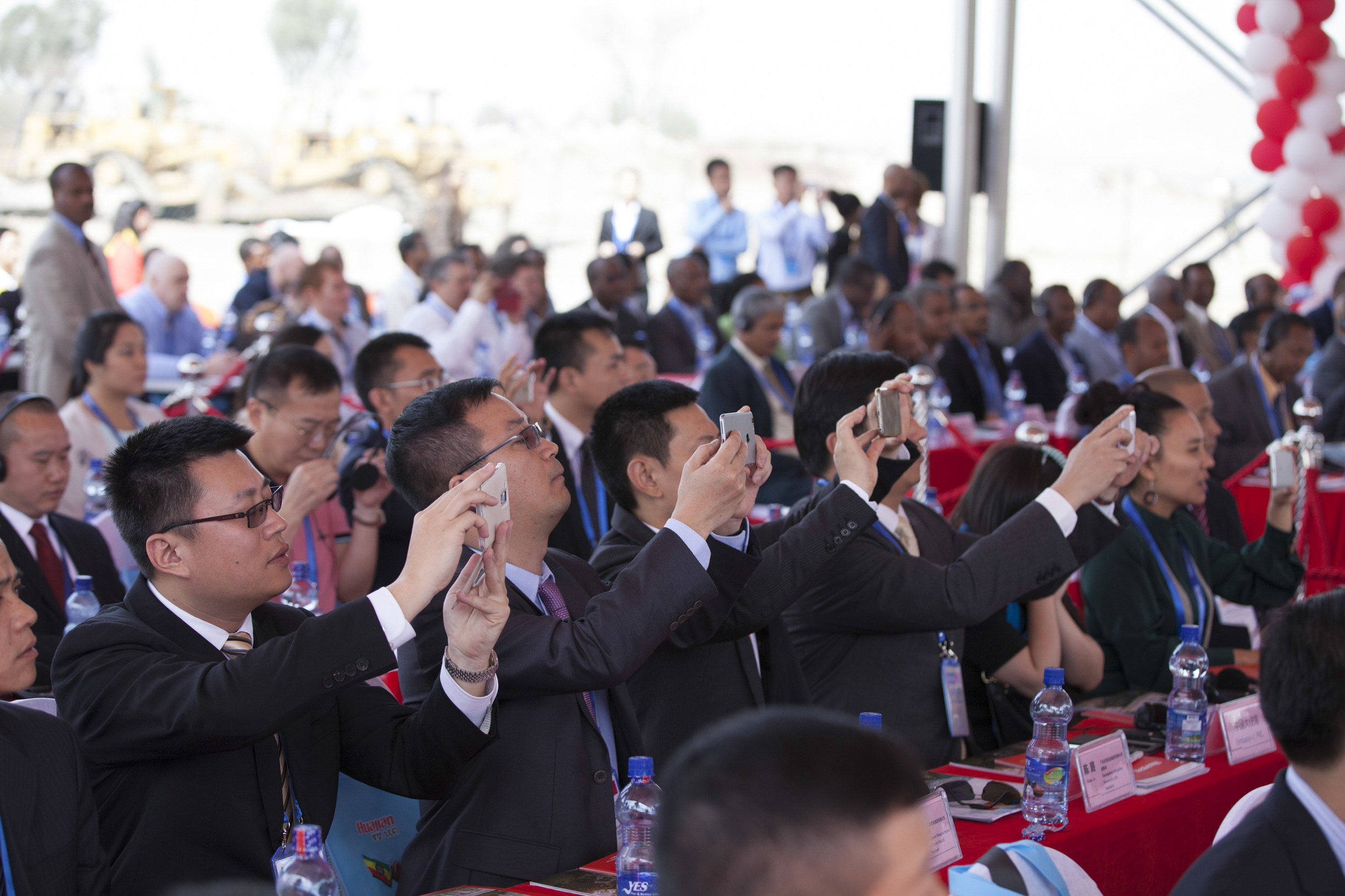 Chinese businessmen are pictured taking photos with their phones during the opening ceremony for the groundbreaking of the Ethiopia-China Dong Guan Huajian International Light Industrial Zone outside of Addis Ababa on 16 April 2015. AFP Photo / Zacharias Abubeker