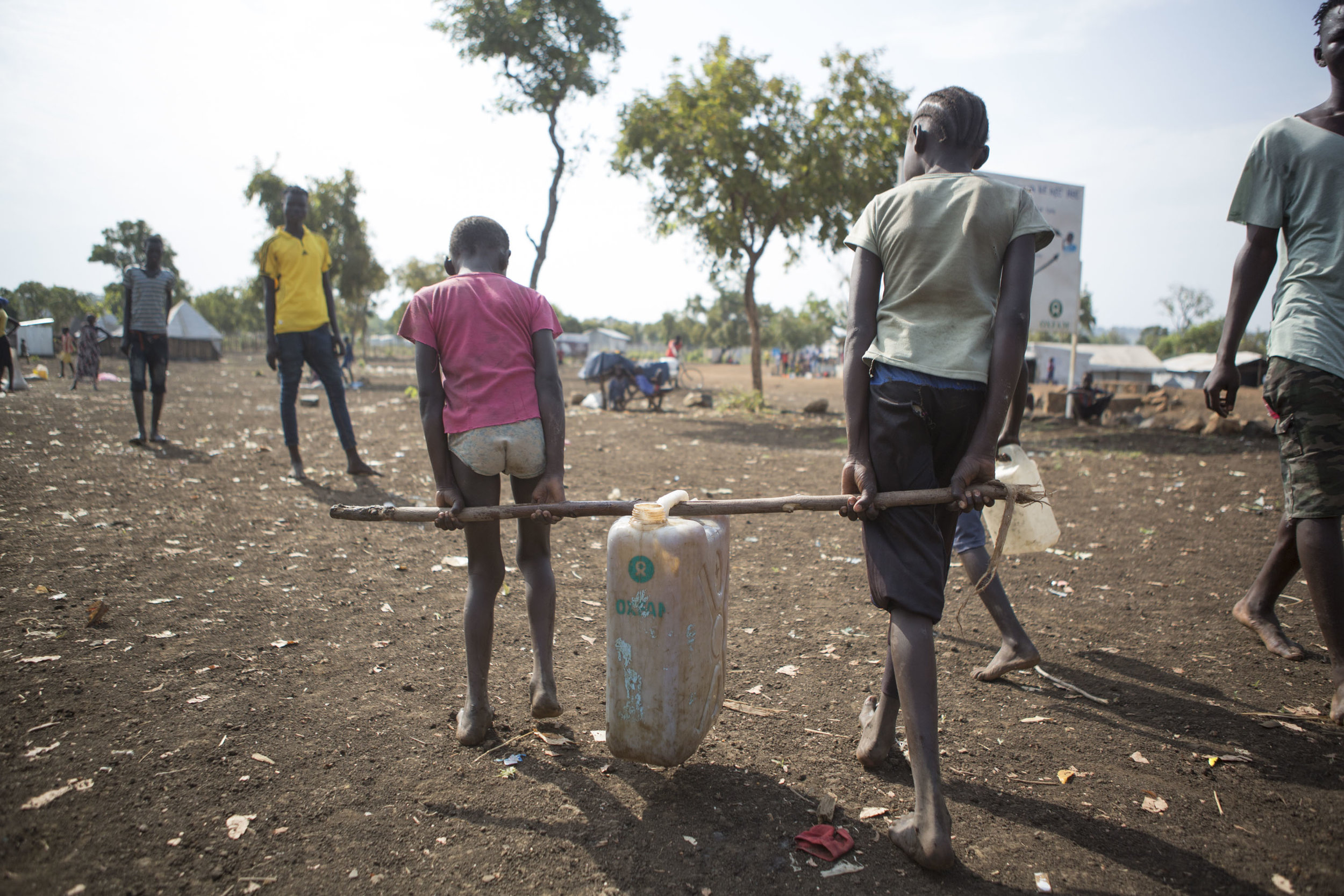 Two girls carry back a jerry can of water together in the Nguneyyiel  refugee camp in the Gambella region of Ethiopia on 26 Nov 2017. MSF / Zacharias Abubeker