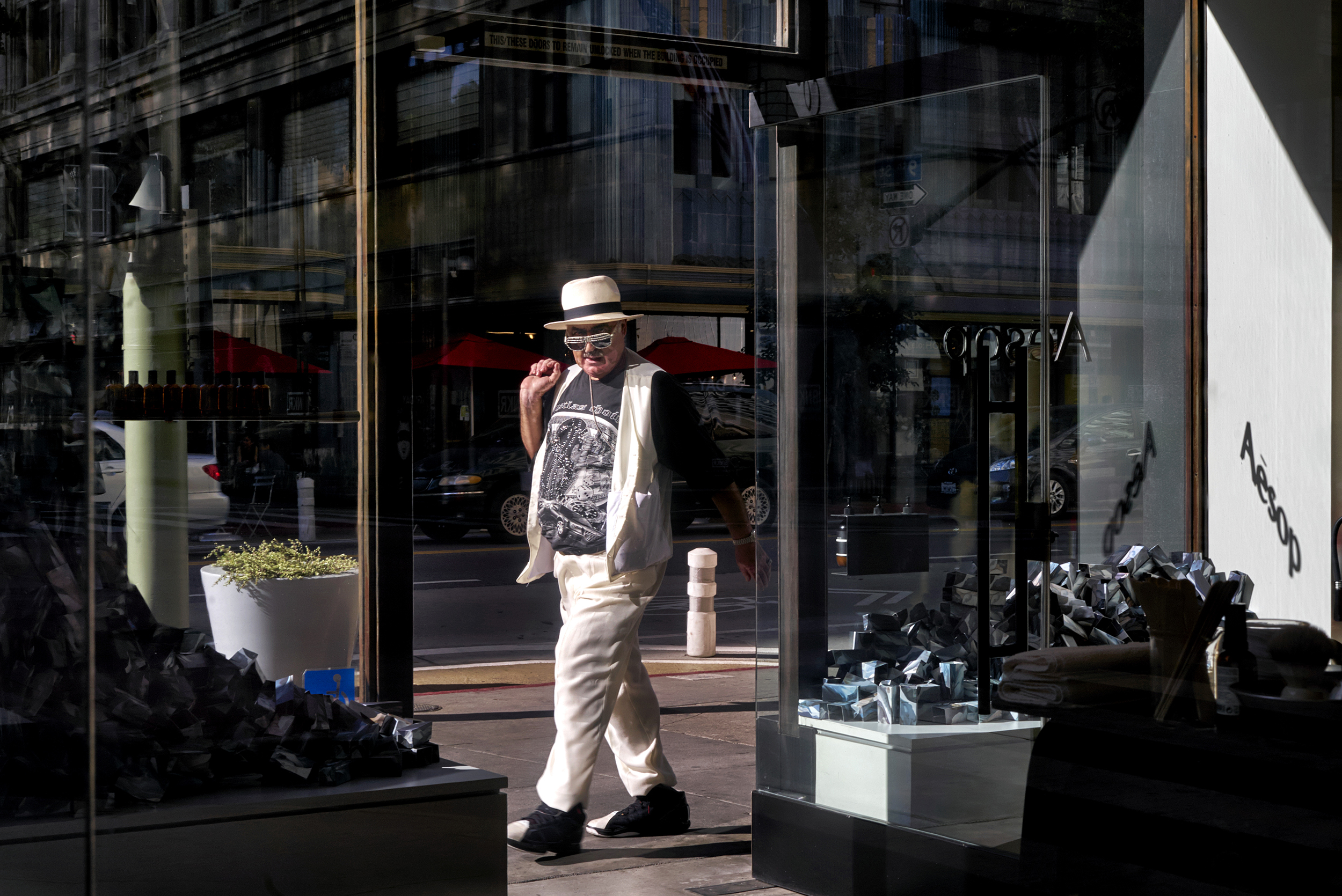 person-walking-by-store-front-dtla-los-angeles-street-photographer.jpg