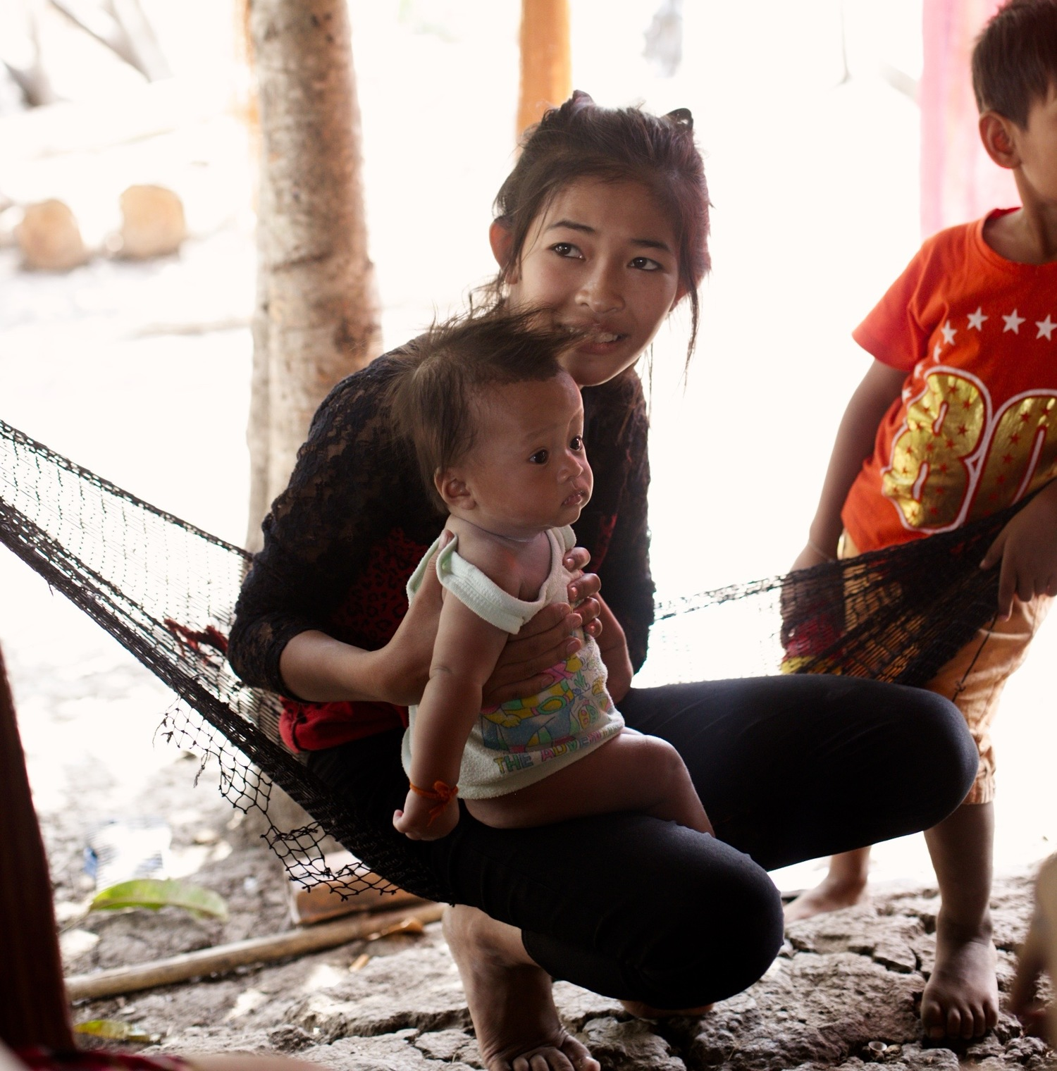 Srey Pich and her new baby in their hut.