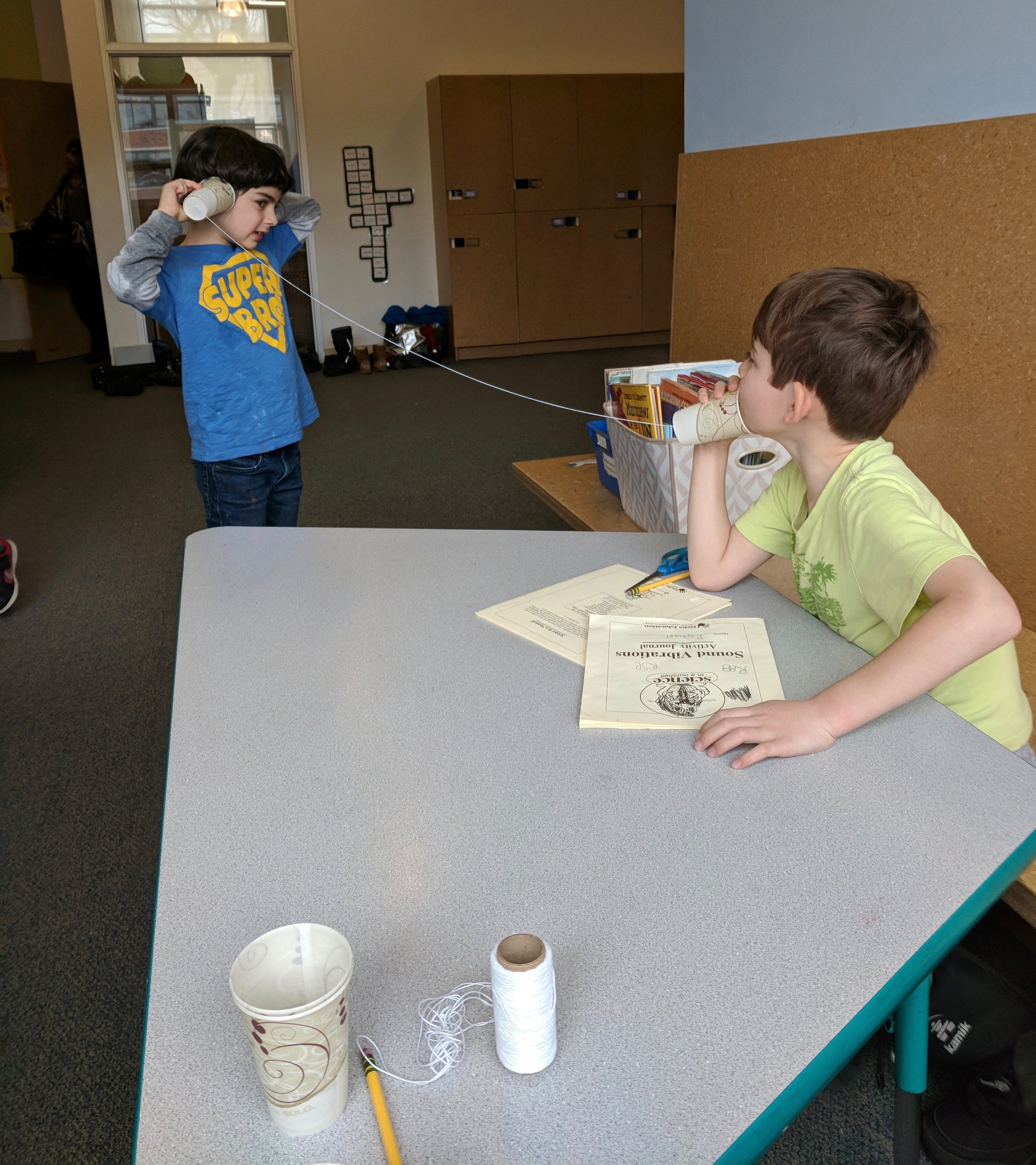 Second and third graders are learning about sound waves by testing how sound works through string telephones.