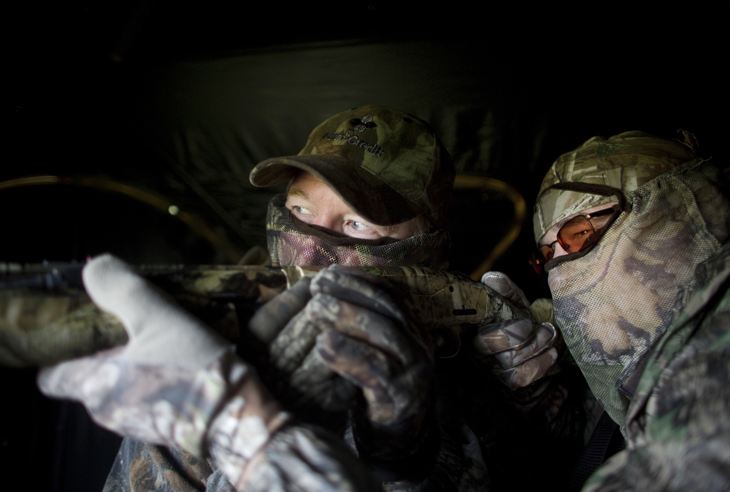 Tommy Meador, left, one of the two sighted guides, looks down the barrel of Mike Doyle's gun and helps point the Mossberg 500 shotgun towards the decoys as Doyle, right, also keeps his eyes open as they sit inside of a ground blind practicing during their hunt. Meador has helped out with the hunt for the past six years.