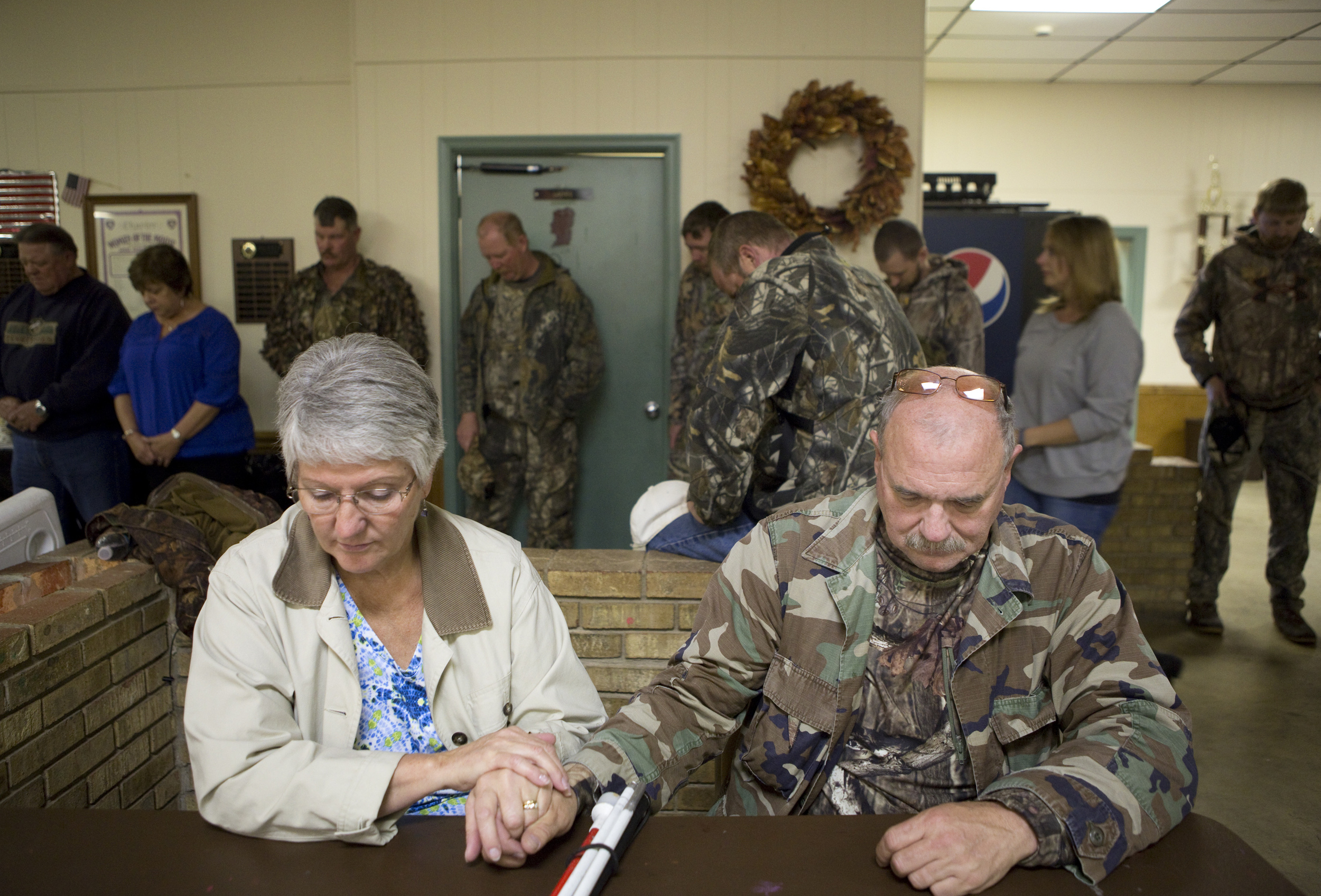 Terry Doyle, left, holds Mike's hands during prayer for the after-hunt meal. Hunters reconvened at the Moose Lodge in Bedford to fill their stomachs and also received awards and prizes for their efforts. The Doyles stayed at the Days Inn in Bedford the night before. Terry stayed behind at the hotel to catch up on a few more hours of sleep after driving Mike there.