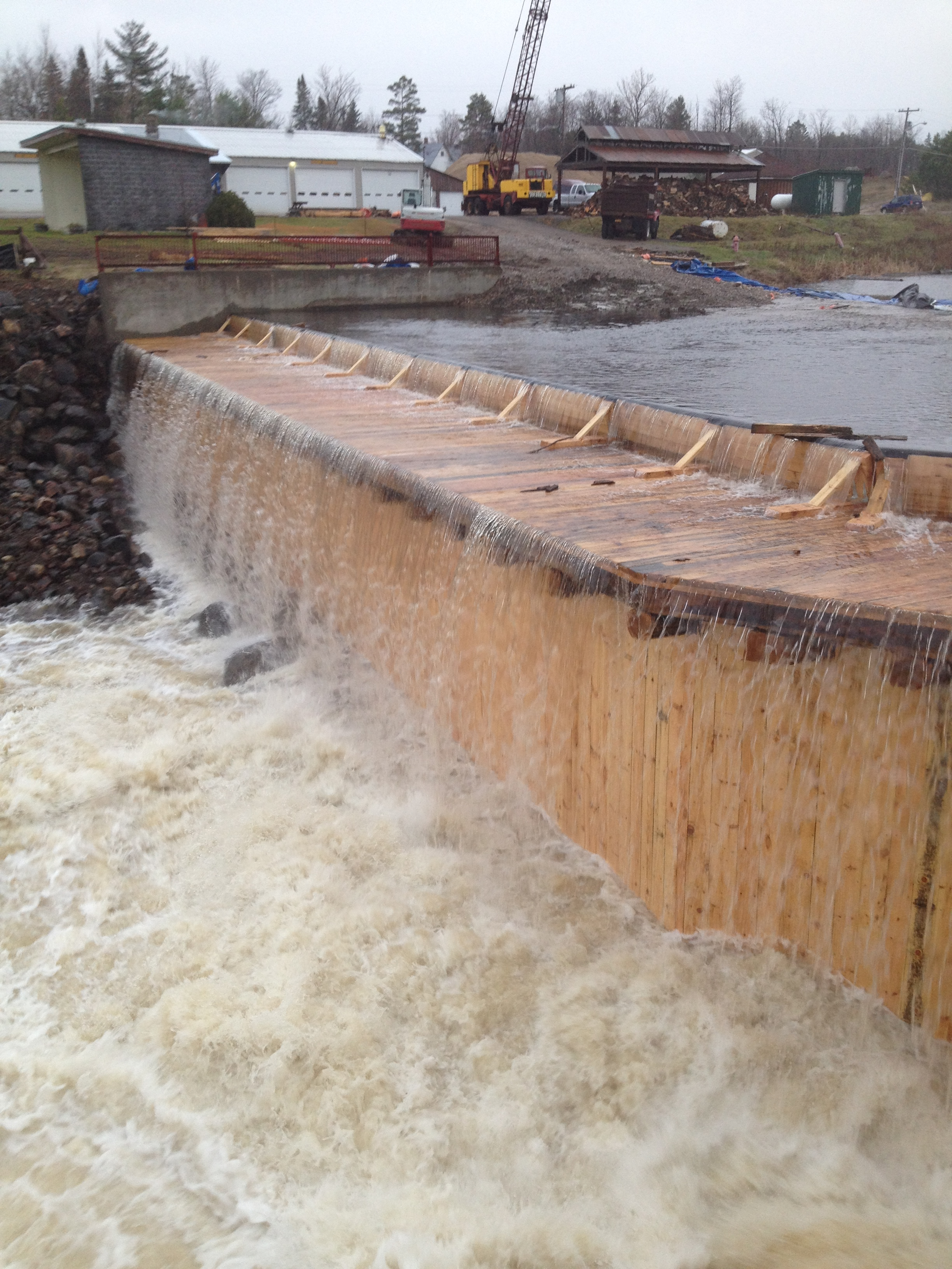 Water spills over the completed dam for the first time.