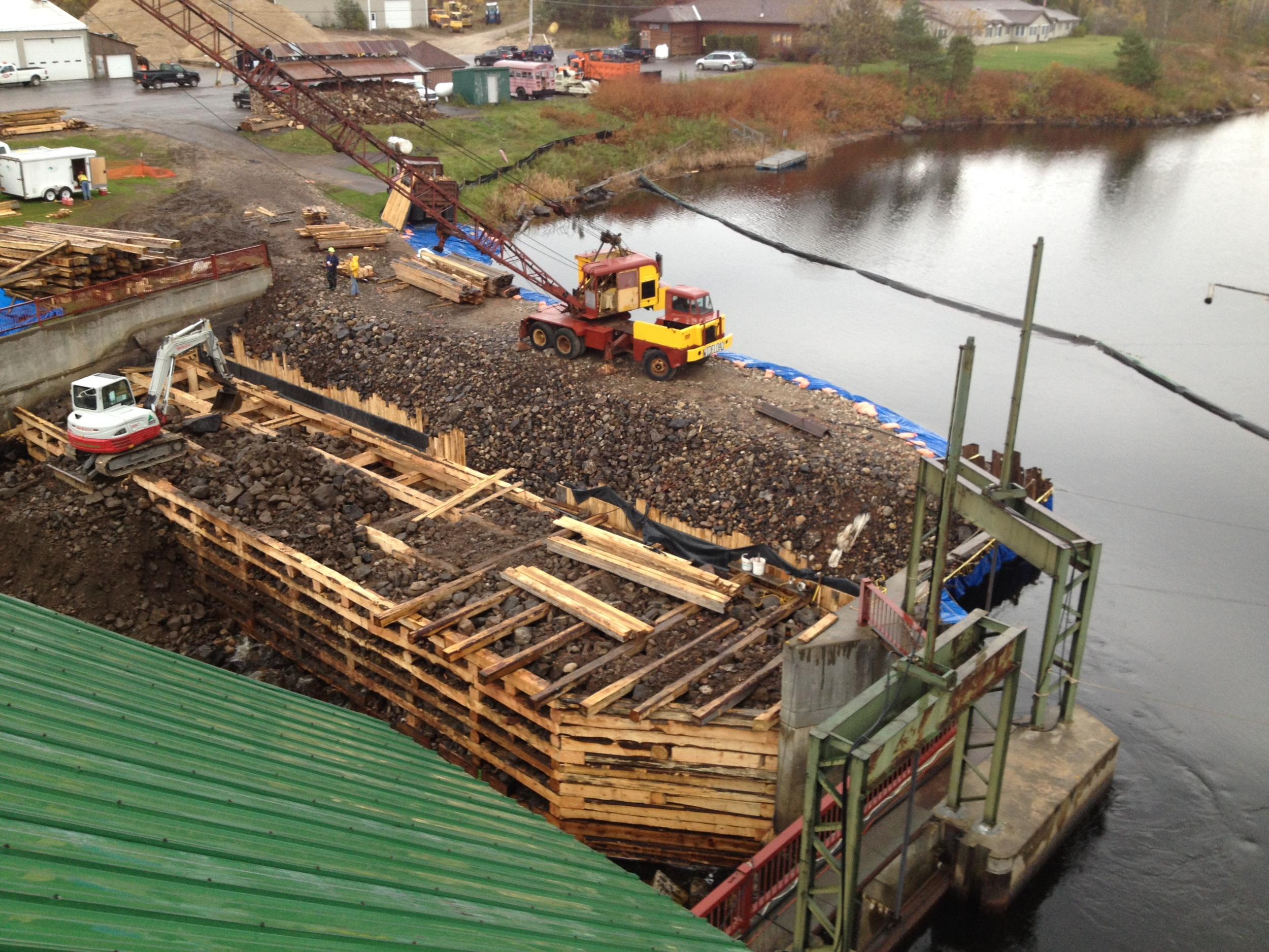 The rock coffer dam diverted water from the work site and made a spot for thecrane, which picked logs from shore and set them in place.