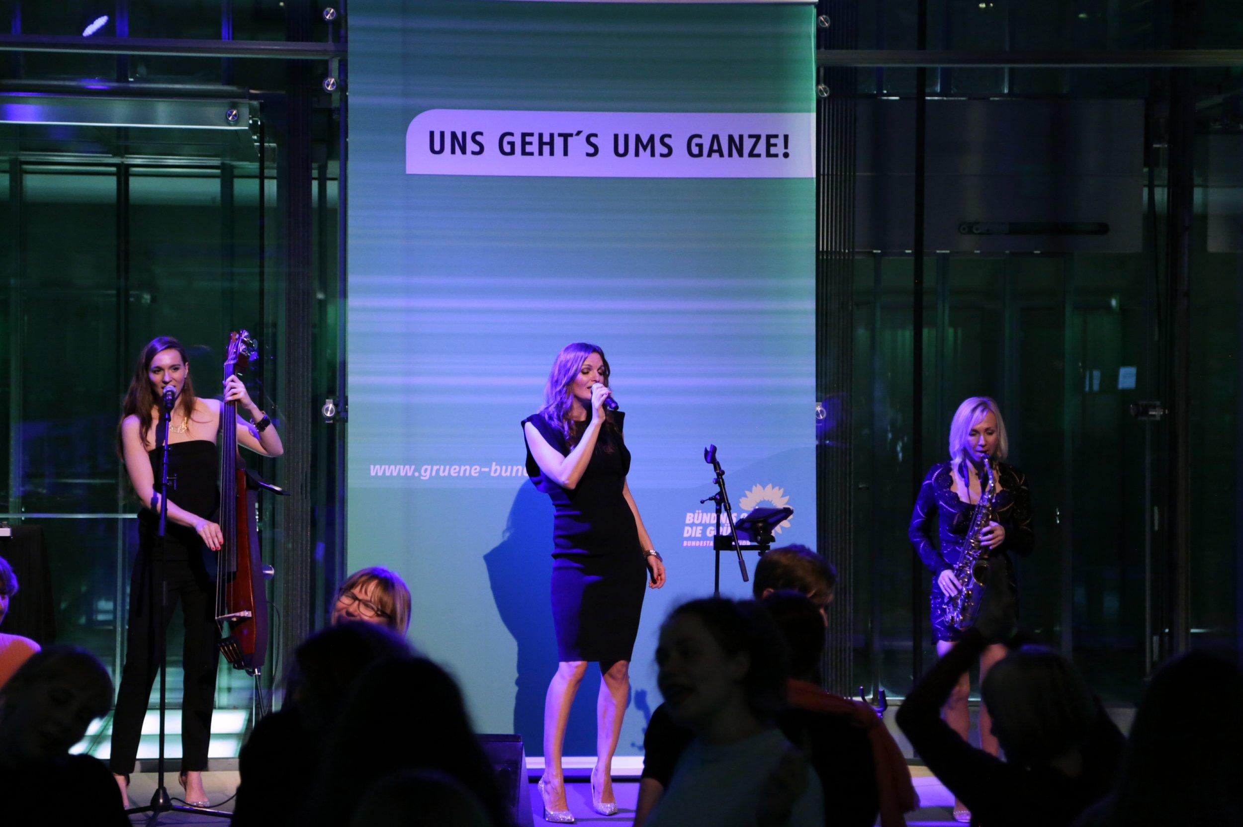 Frauentrio Sunset Orange mit Moderatorin und Sängerin iza Höll im Bundestag zum Frauentag