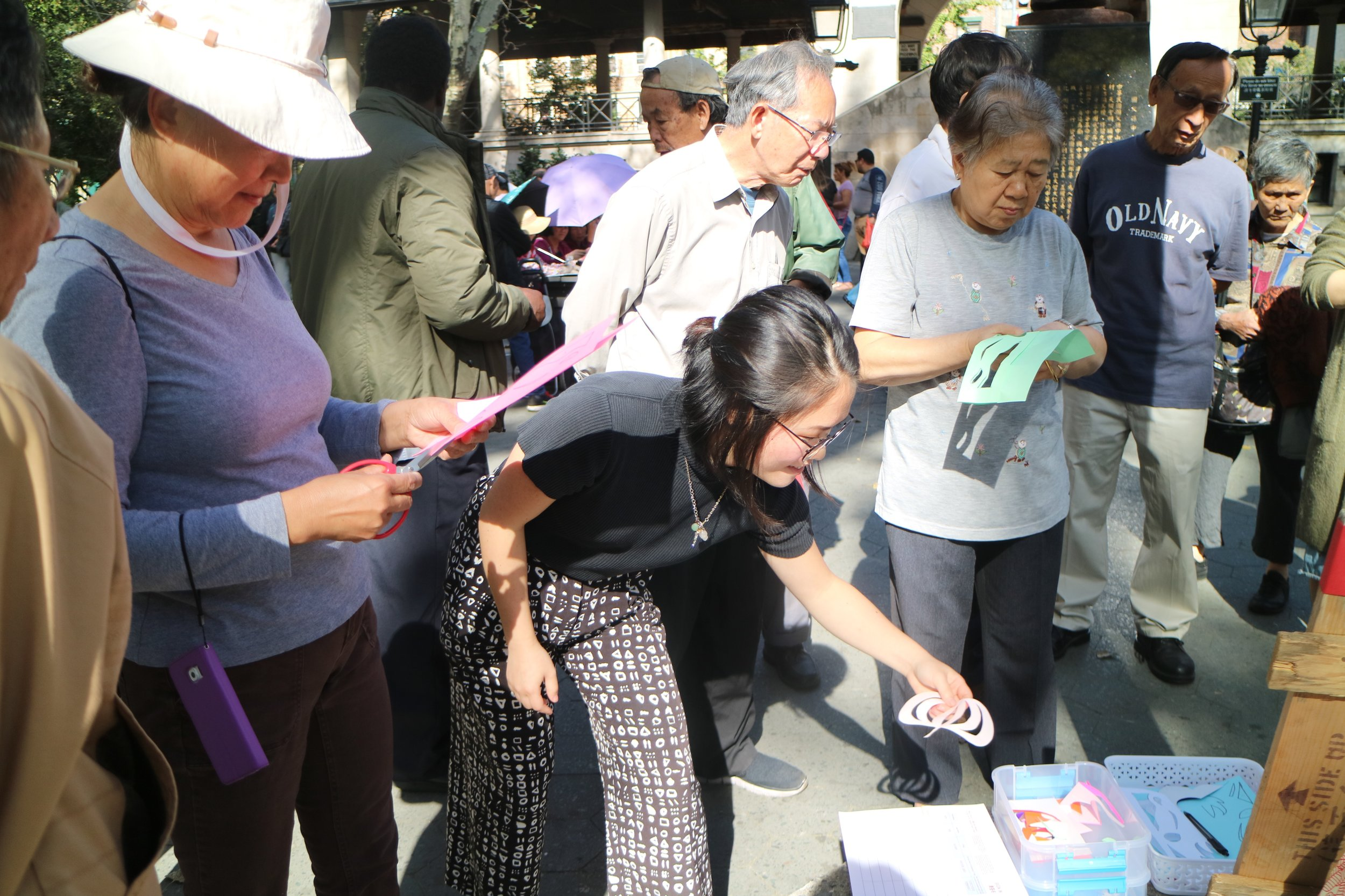 Residency Coordinator Clara Lu makes paper cuts with community members in Columbus Park for a W.O.W. Shadow Puppet Theater free workshop. Image credit: Mei Lum // 在W.O.W.的免费『皮影戏院』项目上,驻地项目协调员Clara Lu在哥伦布公园和社区成员们一起做剪纸. Mei Lum摄
