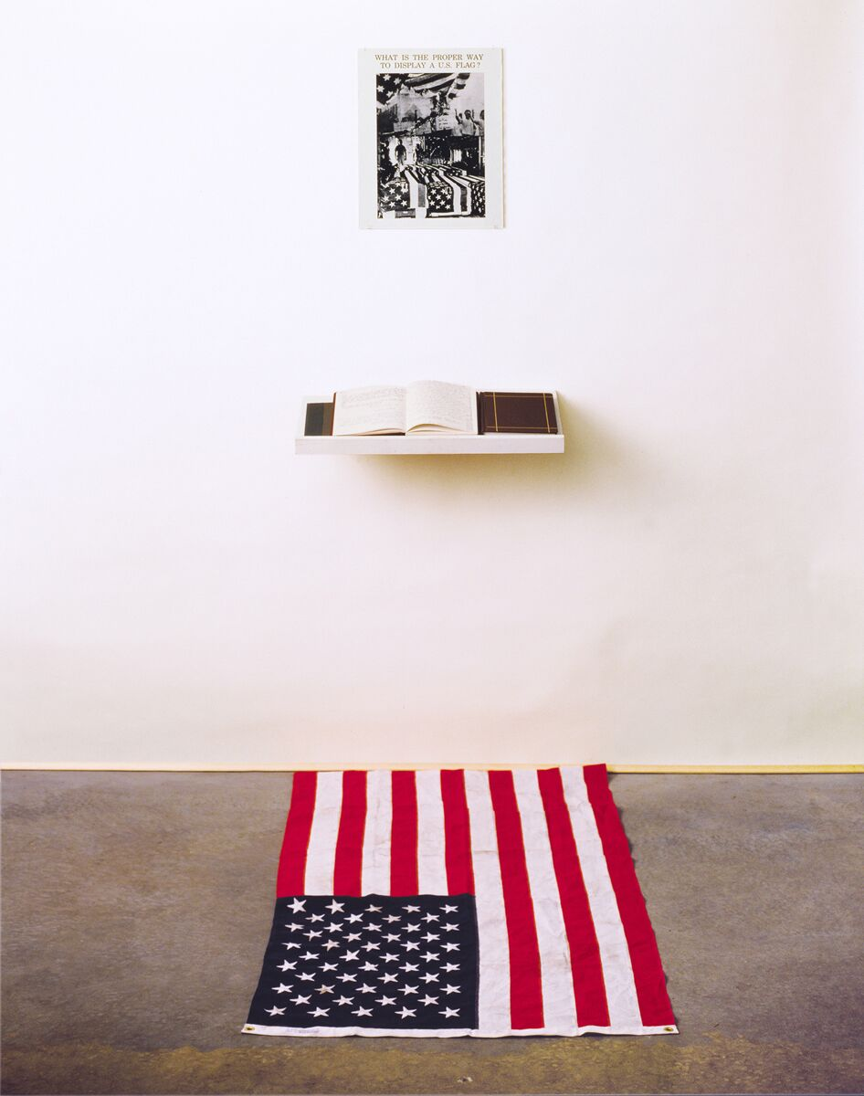 What is the Proper Way to Display a US Flag? ( installation for audience participation,) 1989   Photomontage including images of flag-draped coffins and South Korean students burning US flags; a shelf with a blank book inviting visitors to write responses; and, an American flag on the floor requiring visitors to decide whether to step on the flag to submit their feedback.    Courtesy the artist Image courtesy the artist.