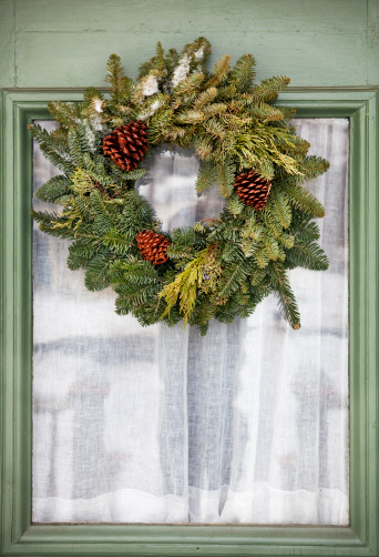 A nice evergreen wreath with a few small pinecones. Loving the color of that door, too!