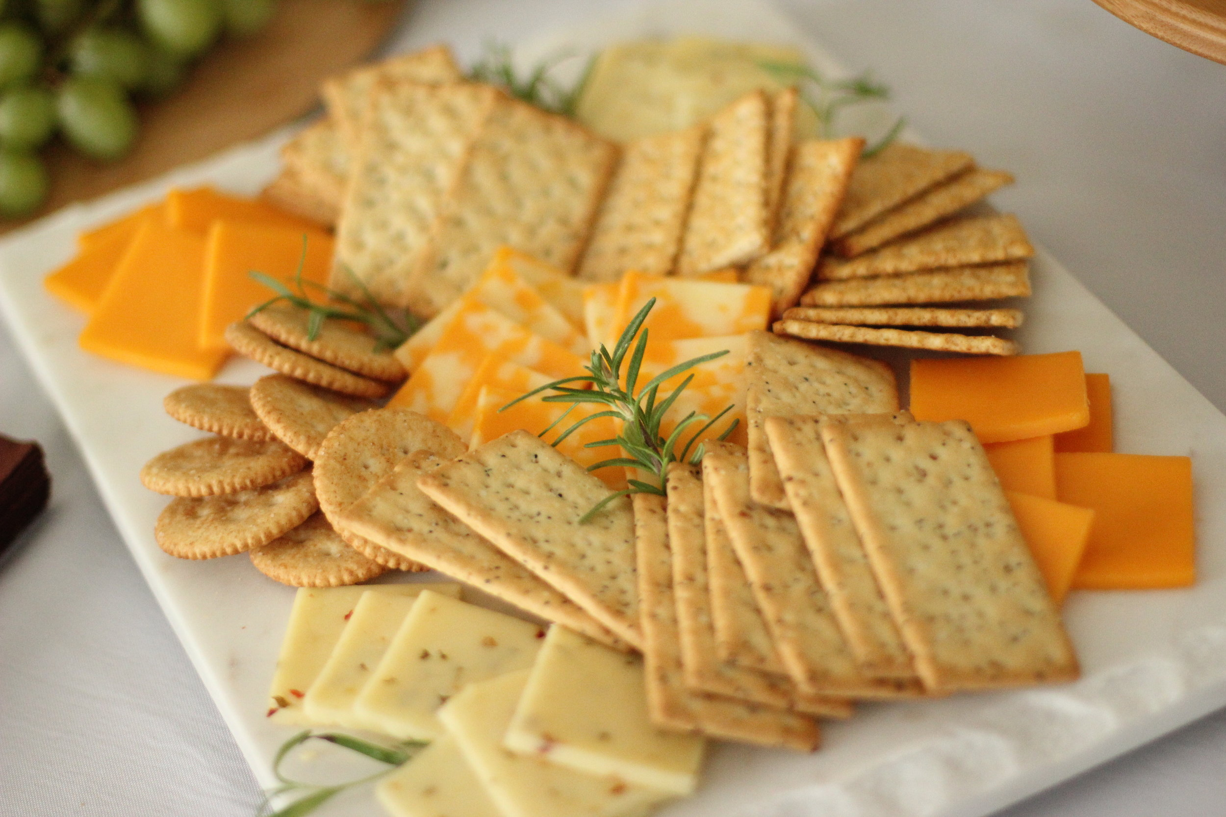 cheese and cracker tray with fresh herbs