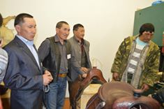 Master saddle maker, Seremei (second from left), and region governor in new workshop.