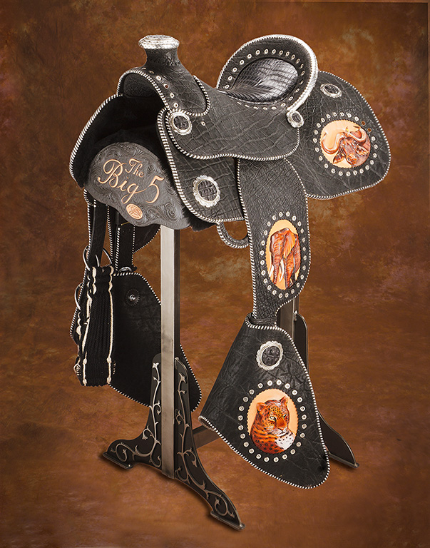 """""""  Big Five"""" collection saddle. Features: LEGAL black elephant and crocodile leather; sculpted, hand carved, and painted portraits of the Big 5 African animals; all silver sterling and FINE (including edges and braiding); spots are actual 45 long caliber cartridges. Comes ready to display on the custom stand. A truly unique piece of work that took 700 hours to construct! Fully rideable….and one-of-a-kind!      Price: $48000.00"""