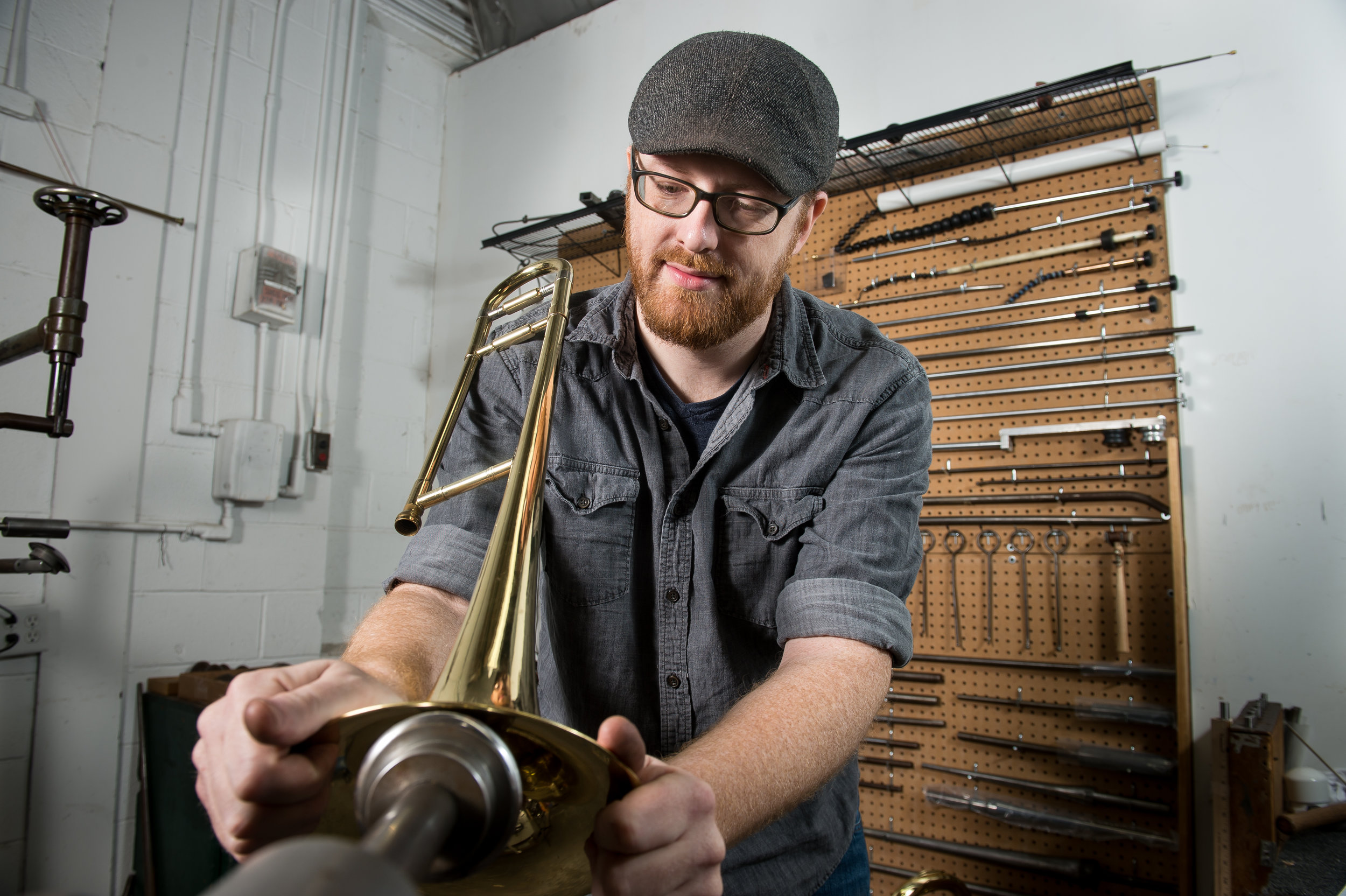Dane Mountain, Brass Shop Manager repairs the bell on a trombone in the Zeswtiz Music Workshop