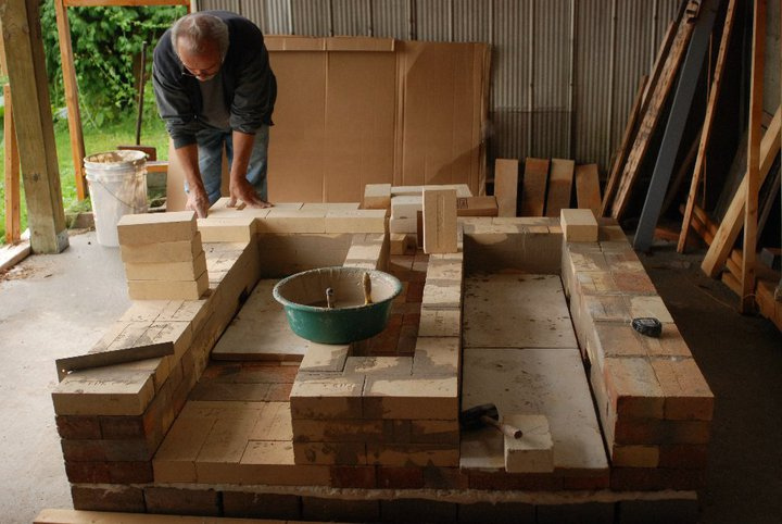 Joseph building the base walls of the kiln. The bottom of the fire boxes and the flu to the chimney can already be seen.