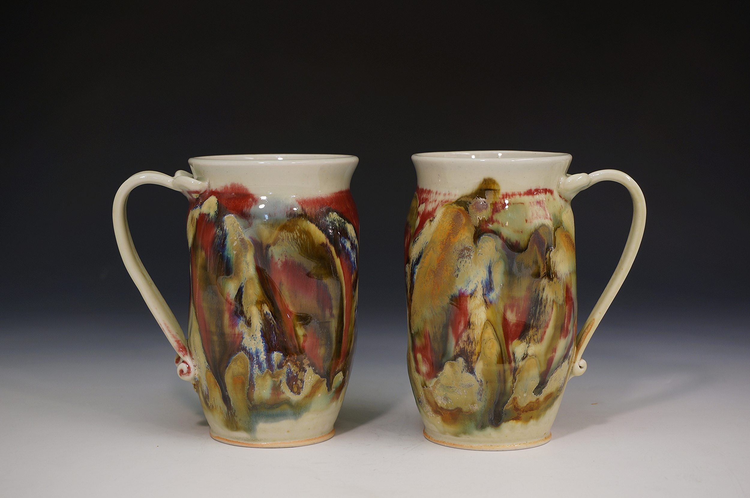 2 sanity mugs in copper red, reduction wood fired with oxide decorations.
