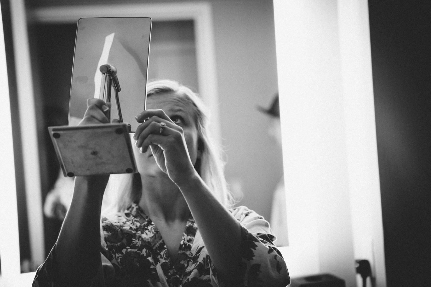 Bride checking her makeup in mirror