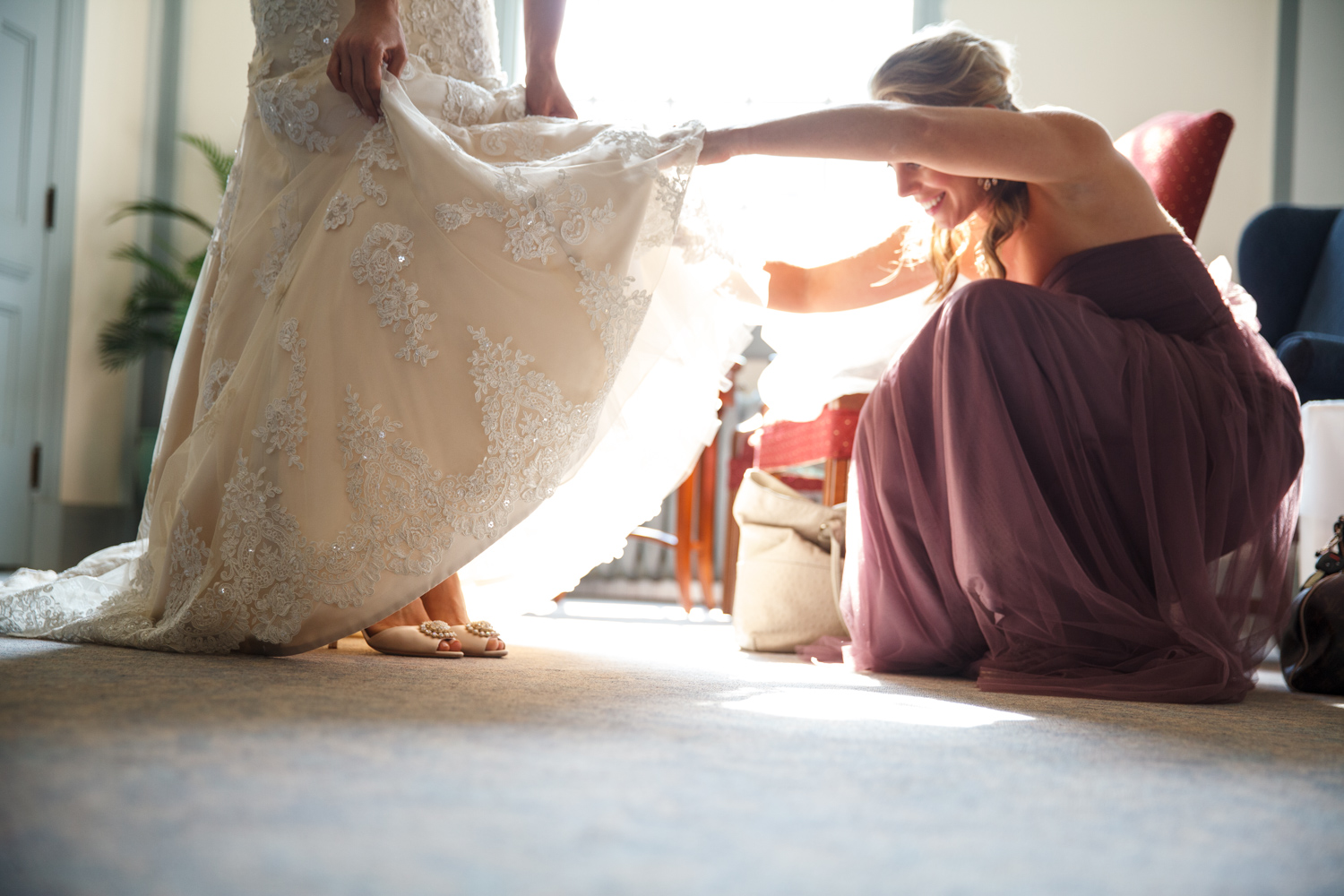 Sister helps bride with her shoes