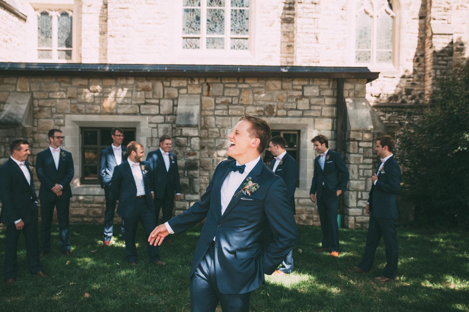 Groom laughing at groomsmen