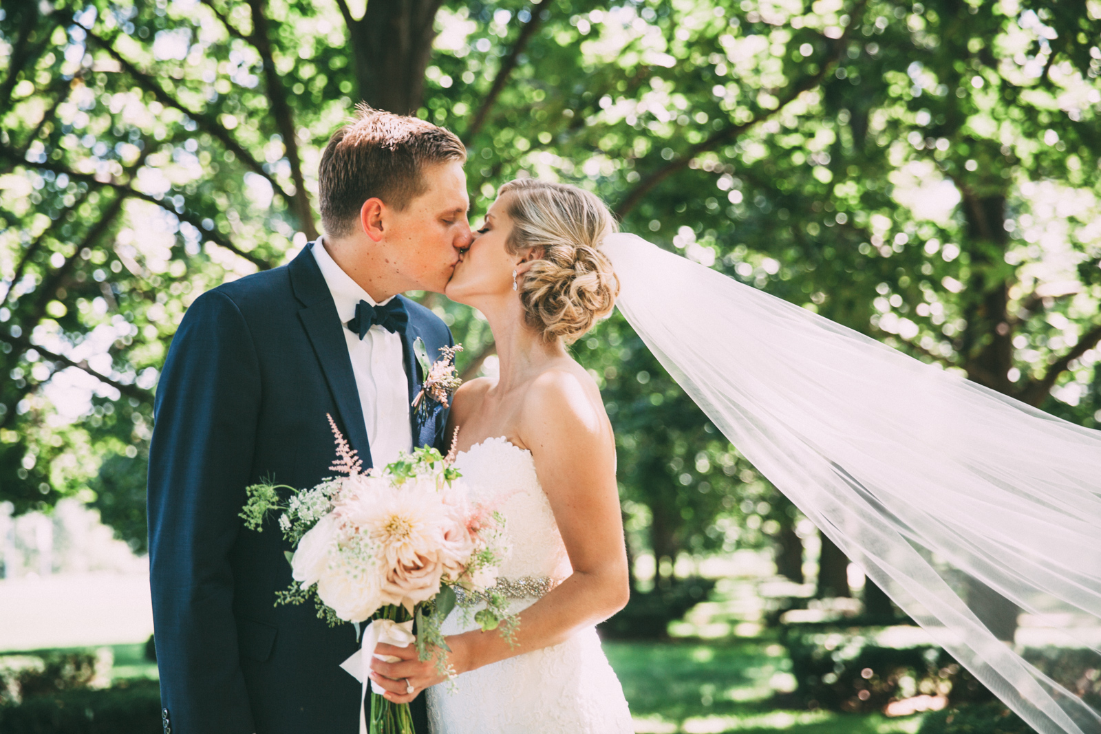 Bride's veil blowing in the breeze while she kisses the groom