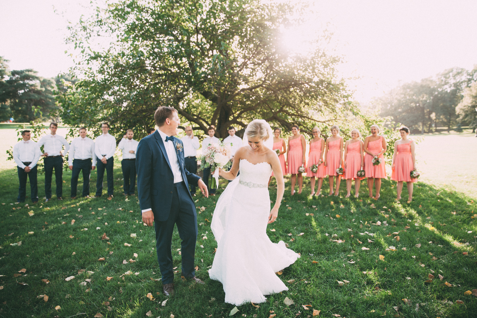 Bride and groom laughing with wedding party in the country